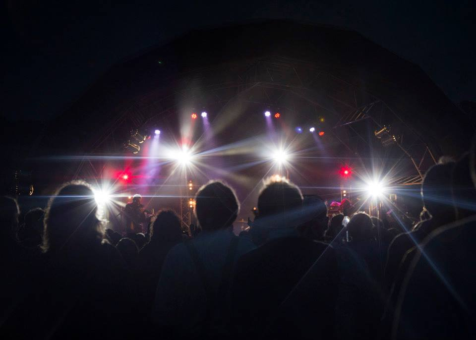 audience shot of a live show with red and white lighting