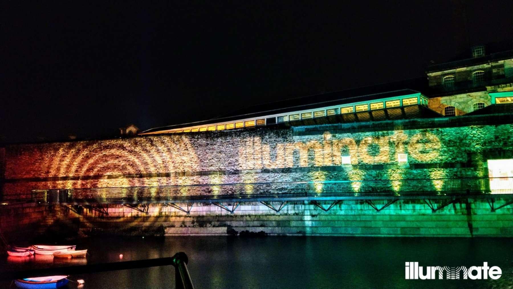 Illuminate logo projected onto uplit exterior wall