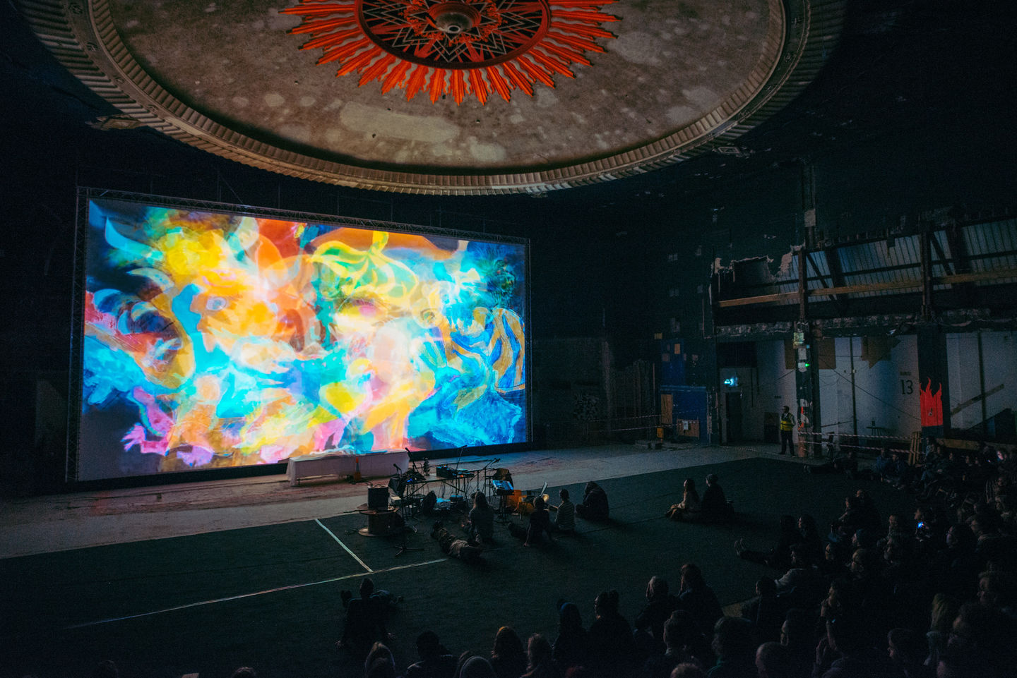 large screen in disused venue with audience area